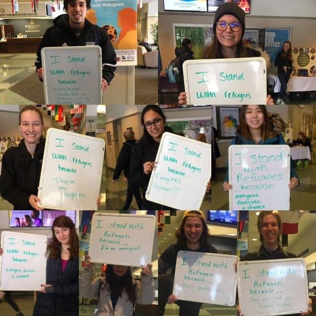 """Students standing with signs saying """"I stand with refugees because..."""" followed by a reason"""